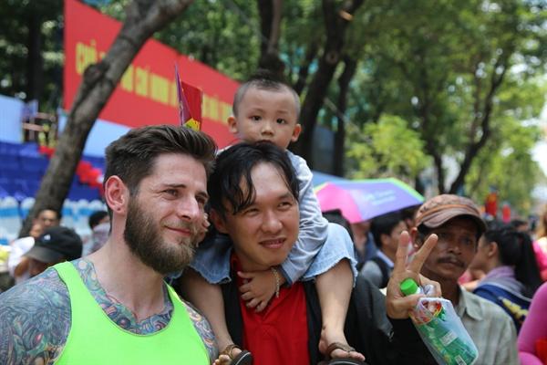 베트남 해방 및 통일 40주년을 기념해 4월 30일 오전 호찌민 시내 레 주안 거리에서 열린 통일 싸이클 대회에 참석한 한 외국인 선수가 구경 나온 베트남 시민과 기념촬영을 하고 있다.
