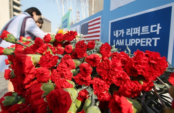 보수단체 자유한국청년회 회원들이 3월 6일 서울 종로구 세종대로 주한 미국대사관 인근에서 마크 리퍼트 주한 미국대사의 쾌유를 기원하는 의미로 카네이션을 펼쳐놓고 있다. 이 단체에 따르면 카네이션은 리퍼트 대사의 고향인 미국 오하이오주를 상징하는 꽃이다.