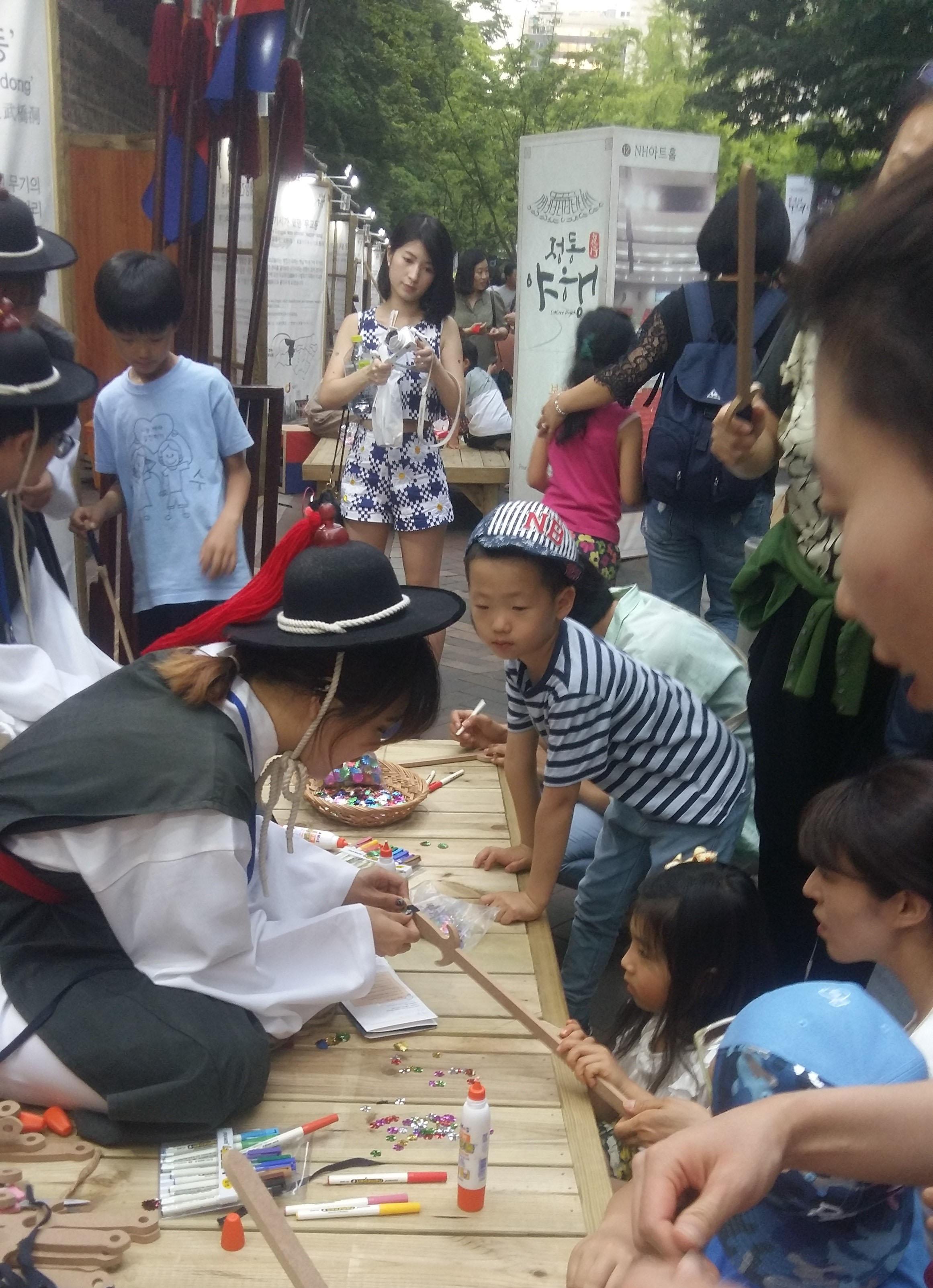 덕수궁 일대에서 열리고 있는 '정동야행' 축제에서 참가자들이 조선시대 전통무기 만들기 체험을 하고 있다.