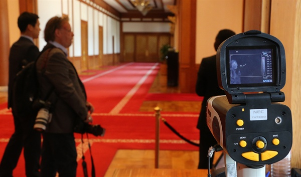 청와대 출입 근무자가 4일 청와대 본관 출입문에 설치된 열감지 카메라로 출입자에 대해 체온을 검사하고 있다.