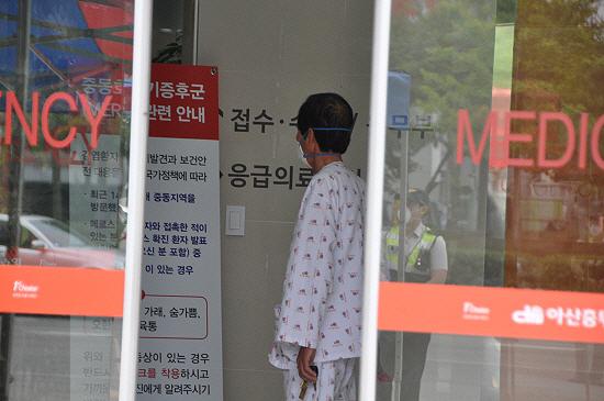 아산충무병원에 격리된 한 환자가 메르스관련 안내문을 살피고 있다.
