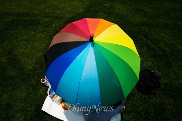28일 오후 서울광장에서 열린 퀴어문화축제에서 한 참가자가 무지개 우산을 쓰고 있다.
