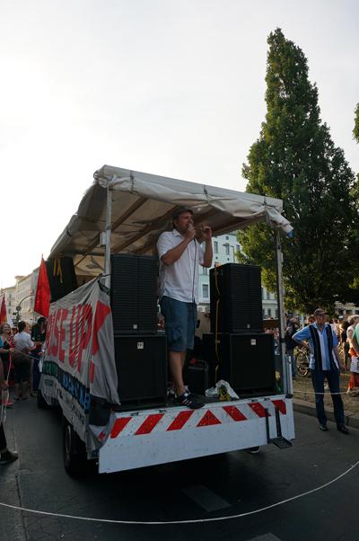 그리스 연대시위 집회 진행 차량 위에서 한 남성이 연설을 하고 있다.