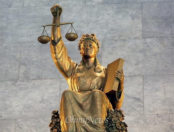 서울 서초구 대법원 대법정 출입문 위에 설치된 '정의의 여신상'. 오른손에 천칭저울을 글고 왼손에는 법전을 안고 있다.