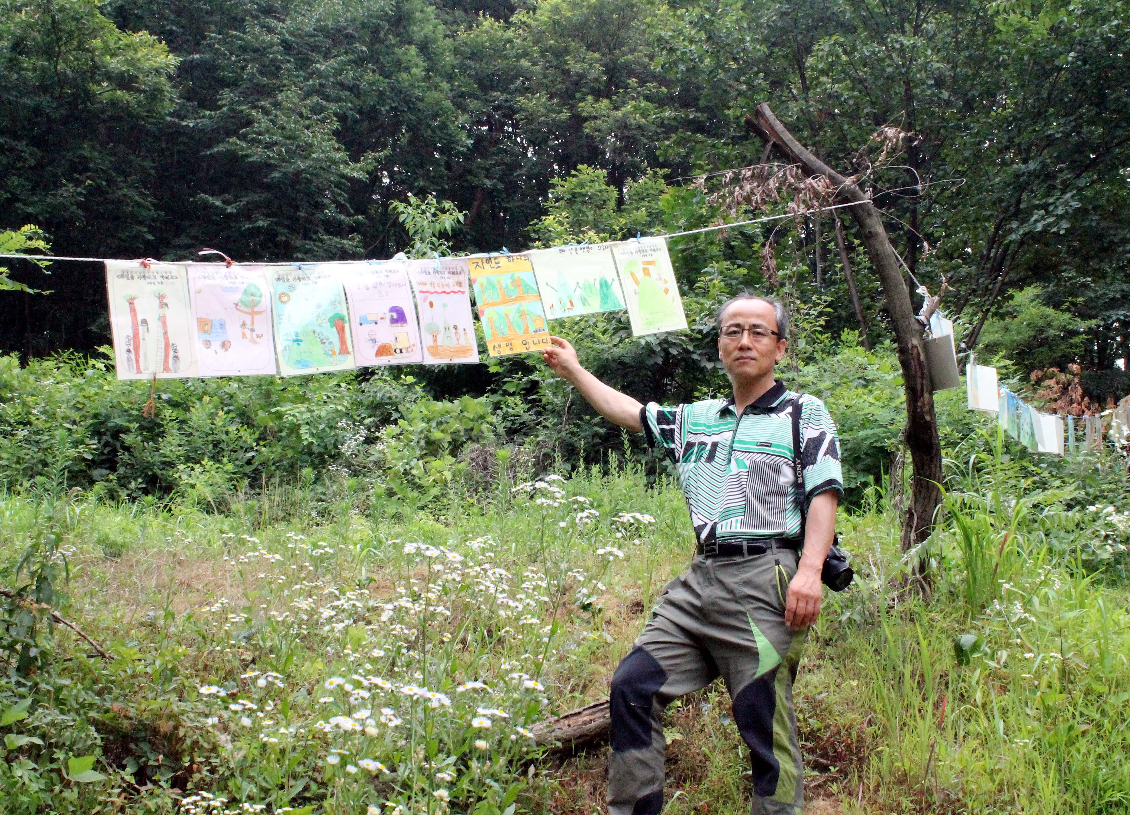 지곡초등학교 학생들이 용인 부아산에 붙인 그림을 최병성 목사가 가리키고 있다.