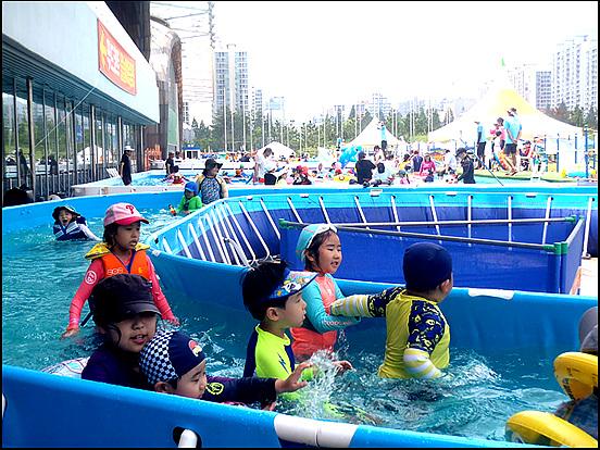 세찬 물결따라 어린이들이 빙글빙글 돌아가며 물놀이를 즐기고 있다.
