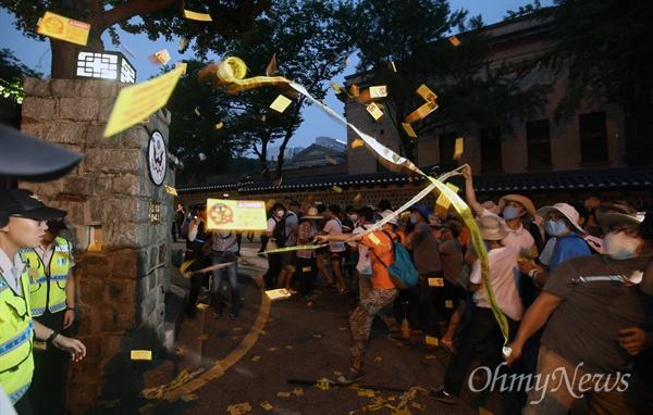 15일 오후 서울 대학로에서 열린 8·15 반전평화 범국민대회 참가자 중 일부가 서울 정동 미대사관저 앞에서 기습시위를 벌이며 탄저균 국내 반입을 규탄하는 전단을 뿌리고 있다.