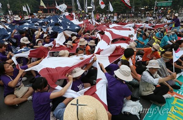 15일 오후 서울 대학로에서 열린 8·15 반전평화 범국민대회 참가자들이 종각사거리까지 행진 후 정리 집회를 하며 미국 성조기와 일본 욱일승천기를 합친 대형 깃발을 찢는 퍼포먼스를 하고 있다.