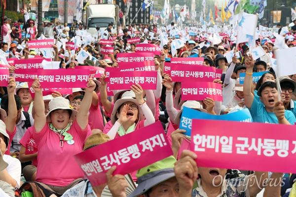 15일 오후 서울 대학로에서 열린 8·15 반전평화 범국민대회 참가자들이 '한미일 군사동맹 저지' 손팻말을 들어보이고 있다.