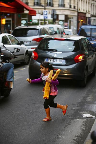바게트를 안고 뛰어가는 소녀.