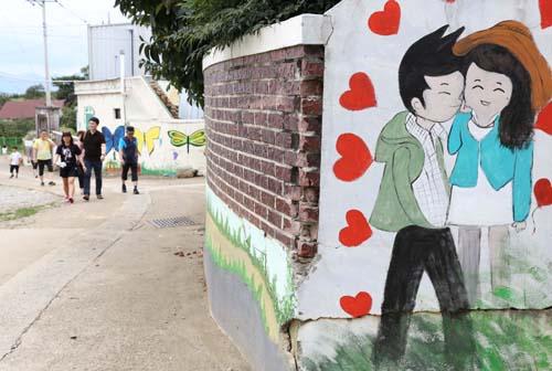 명옥헌원림으로 가는 길목에 그려진 벽화. 여행객들이 벽화가 그려진 골목을 따라 명옥헌원림으로 오가고 있다.