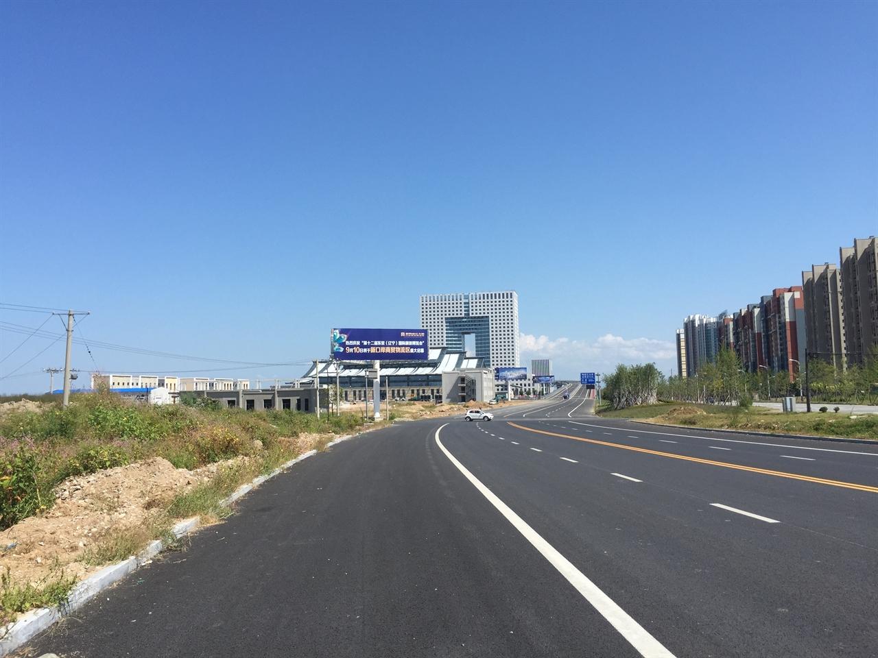 2015년 9월 6일에 신압록강대교와 직접 연결되는 도로 위에서 찍은 사진 위 도로에서 군 경비대가 지키는 대교를 타면 바로 북한 신의주로 연결된다. 신압록강대교에서 내려와 직진하면 랴오닝성 선양과 다롄으로 직접 연결되는 선양~단둥~다롄 순환 고속도로와 연결된다. 중앙에 위치한 사각형의 빌딩은 중조무역 관련 건물로 아직 완공된 상태는 아니었다.