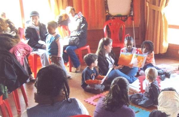 난민학교에서 아이들이 자원봉사자들과 함께 책을 보며 놀고 있다.