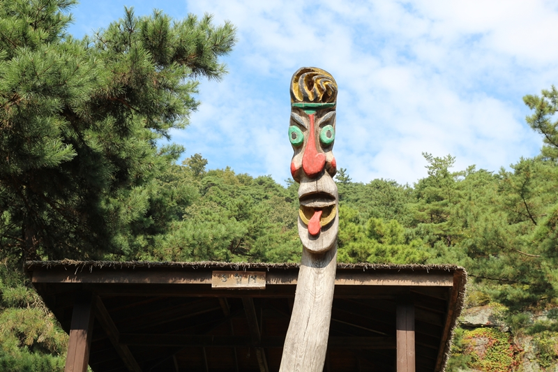 쉼터 앞의 나무장승은 익살맞게도 혀를 빼물고 있다.