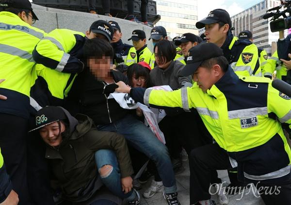 학생들 멱살 잡고 연행하는 경찰 12일 오후 서울 종로구 광화문 이순신 동상 위에서 대학생 10여 명이 올라가 한국사 역사교과서 국정화 강행 처리를 규탄하는 기습시위를 벌이자, 출동한 경찰이 학생의 멱살을 붙잡고 끌어내고 있다.