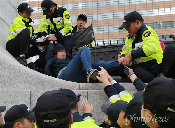 남자 경찰에 사지가 붙잡힌 여학생 12일 오후 서울 종로구 광화문 이순신 동상 위에서 대학생 10여 명이 올라가 한국사 역사교과서 국정화 강행 처리를 규탄하는 기습시위를 벌이자, 남자 경찰들이 여학생의 사지를 붙잡고 끌어내고 있다.