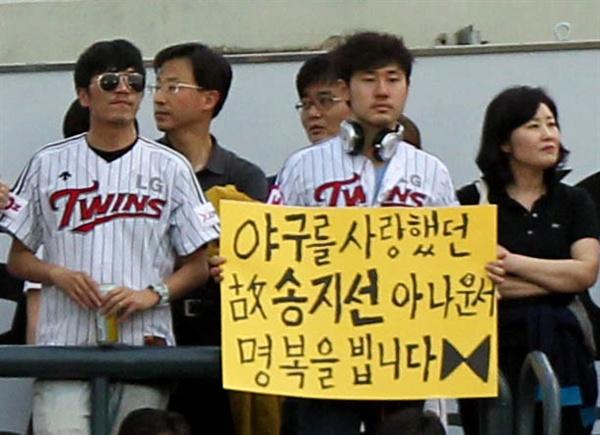 고 송지선 아나운서 명복을 빕니다 지난 2011년 5월 24일 오후 서울 잠실야구장에서 열린 2011 프로야구 LG-두산의 경기. 관중석에서 LG 한 팬이 고 송지선 아나운서의 명복을 비는 피켓을 들고 있다.