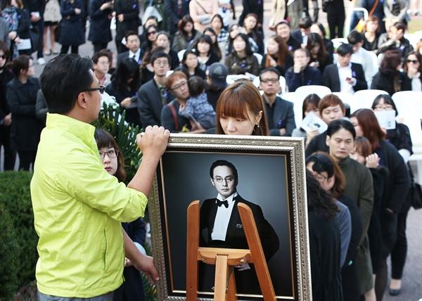 지난 25일 오후 경기도 안성시 유토피아 추모관에서 열린 '신해철 1주기 추모식 및 봉안식'에서 팬들이 고인의 영정사진에 남기고 싶은 메시지를 적고 있다.
