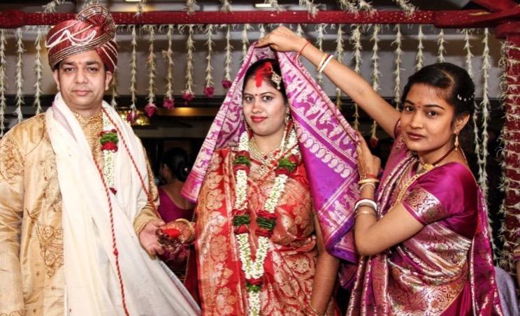 """신랑이 착용한 """"Pagdi"""" 는 결혼식 때 (왕의 모자로도 불리운다) 쓰는 모자로 영광스럽고 성스러운 의미를 부여한다. 신부의 이마와 머리 경계선에 묻어있는 빨간 염료는 혼인을 한 여자를 상징한다. 코에 있는 빨간 표시는 이마에 염료를 바르던 중 실수로 묻어버린 자국이다."""