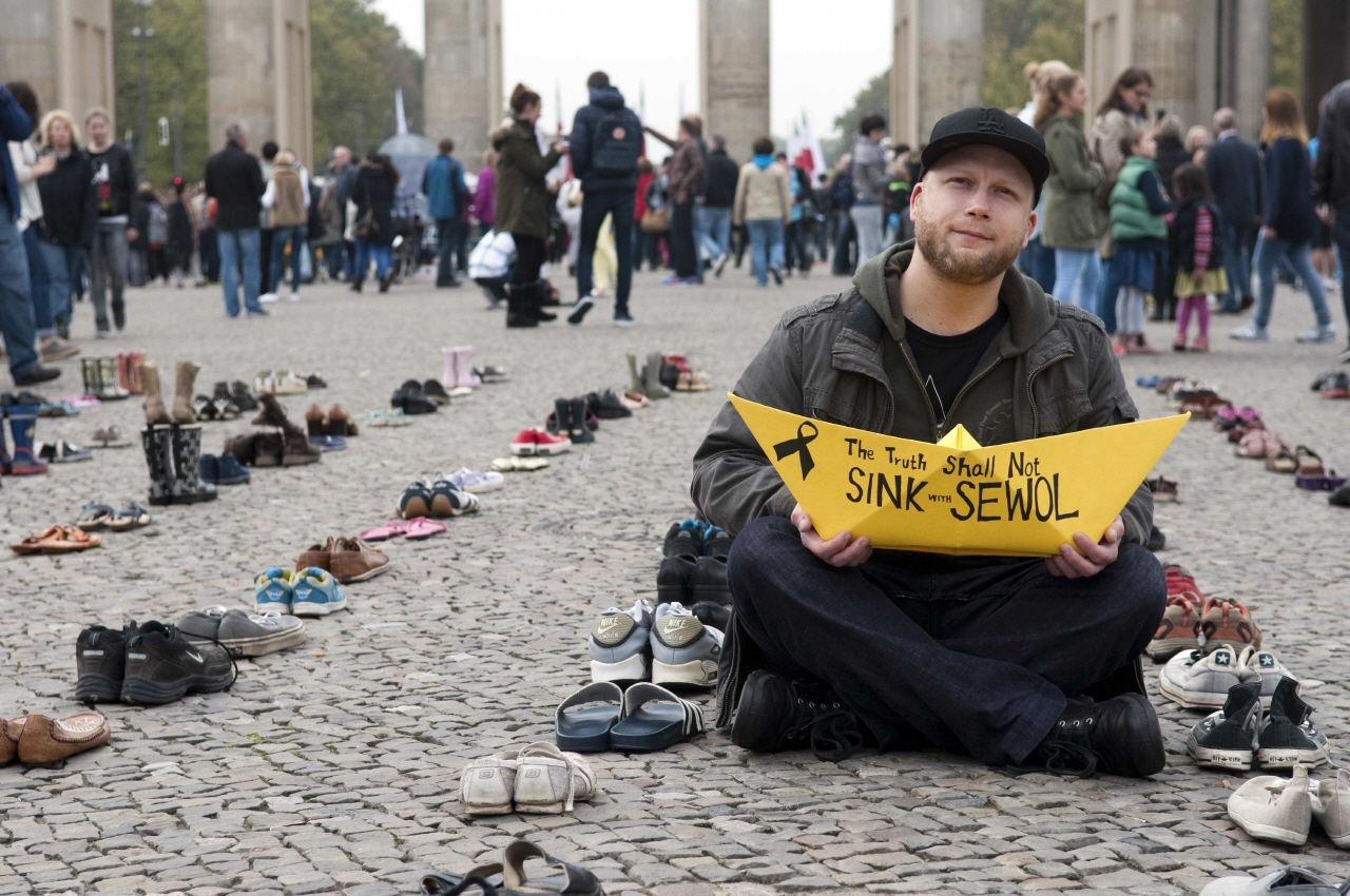 한 남성이 세월호를 상징하는 노란종이배를 들고 있다.