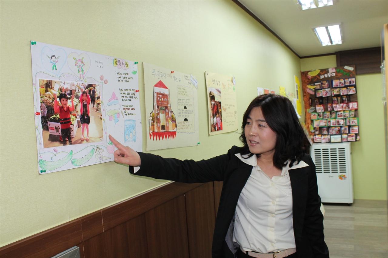 대추동이 문화마을 만들기 공동체 정순옥 대표가 조원시장 내 <작은도서관에>서 동네 아이들이 직접 그린 <조원시장 이야기> 작품을 설명 중이다.