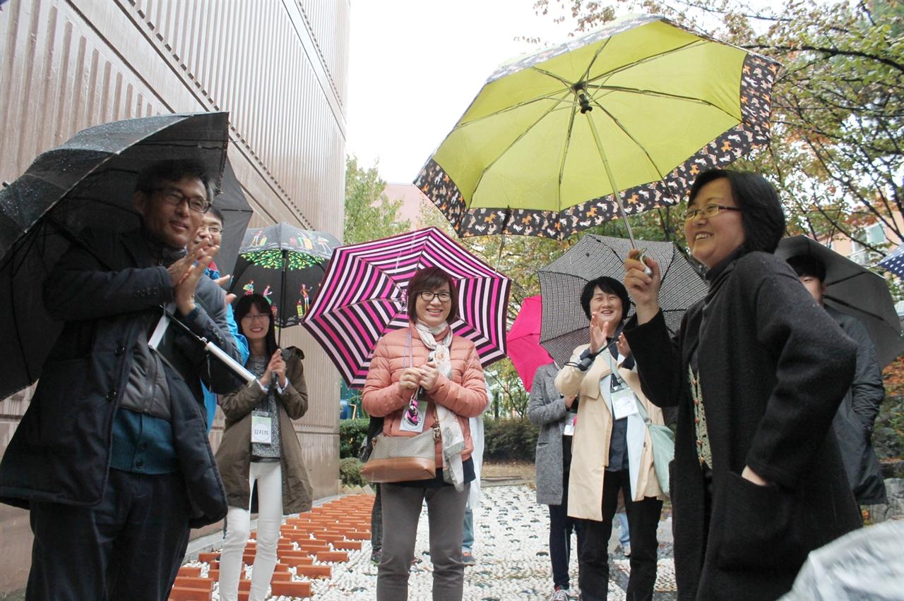 꽃뫼버들아파트를 찾아간 꿈틀버스 사진 오른쪽 노란 우산을 든 분이 꽃뫼버들 아파트에 꽃을 심기 시작해 유명해진 동대표 조안나 선생님이다.