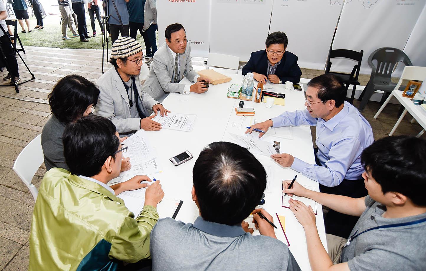박원순 서울시장(오른쪽에서 두번째)이 지난 9월 서울정책박람회 중 서울광장 천막에서 시민들의 정책제안을 직접 받아 검토하고 있다.
