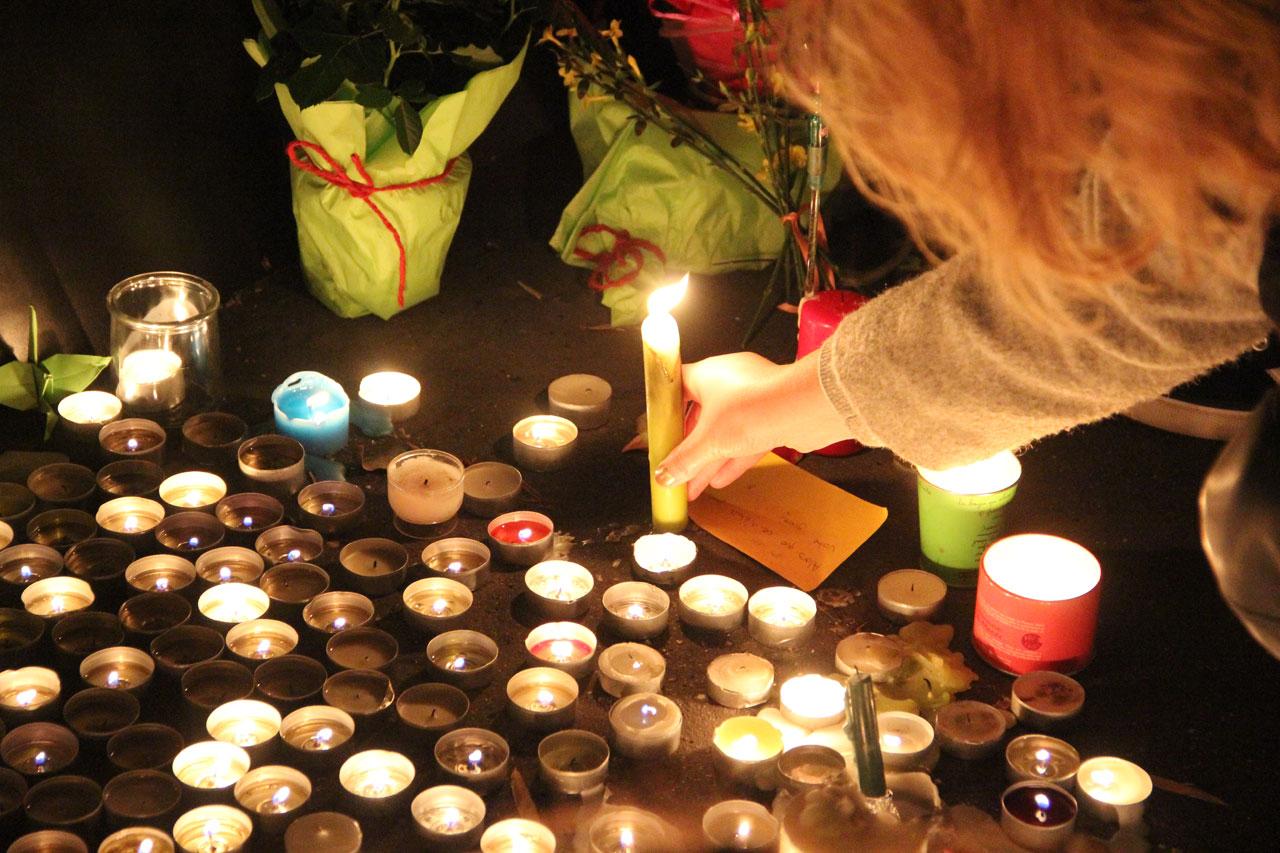 한 여성이 샤론느 길 앞에서 희생자를 추모하기 위해 촛불을 불을 붙여 세우고 있다.