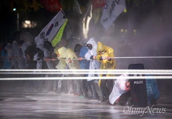 물대포 견디며 차벽 당기기 민중총궐기 대회가 열린 14일 오후 종로1가 종로구청입구 사거리에서 집회참가자들이 밧줄을 이용해 차벽을 쌓고 있는 경찰버스를 끌어내려하자, 경찰이 캡사이신 물대포를 발사하고 있다.