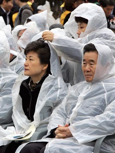 지난 2005년 2월 18일 가랑비가 내리는 가운데 진행된 대구지하철 참사 희생자 추모식에서 당시 한나라당 전여옥 대변인이 박근혜 대표의 비옷에 달린 모자를 씌워주고 있다.