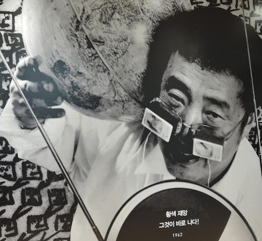 """세종문화회관(미술관)에서 열리는 '백남준 그루브_흥(興)'전 미술관에 게시된 대형사진으로 """"황색재앙, 그것이 바로 나다""""라는 글씨가 뚜렷하게 보인다"""