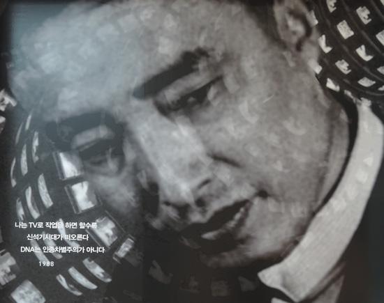 """세종문화회관(미술관)에서 열리는 '백남준 그루브_흥(興)'전 벽에 붙은 대형사진으로 """"TV로 작업을 하면 할수록 신석기시대가 떠오른다""""라는 글씨가 아래 보인다"""