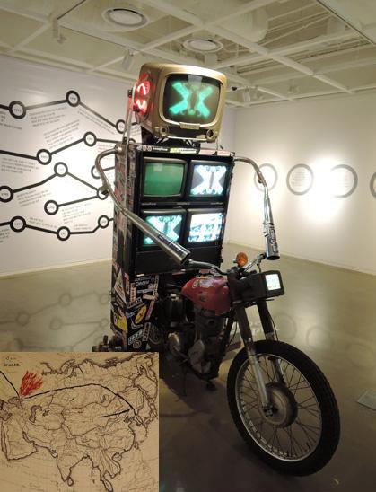 백남준 I '피버 옵틱'(Phiber Optik) 6개 모니터 높이 2m 1995년 작. 1993년 '전자초고속도로'의 연장선상에 있는 작품이다. 지구촌 노마드 전사의 모습으로 분신한 로봇이 오토바이에 TV6대를 싣고 질주하는 모습이 익살맞고 우스꽝스럽다. 아래는 백남준이 고지도에 그린 한국의 유래