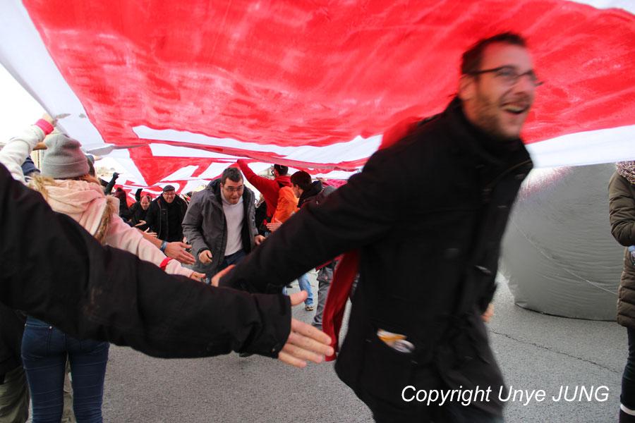 파리회의 190개국 대표들이 이번 회의에서 넘지 말아야 할 선을 상징하는 붉은 띠를 높이 들어 터널을 만들었다. 가두시위에 참여하는 시민들이 환호를 하며 달려가고, 이들을 환영하는 의미로 하이파이브를 해주고 있다.