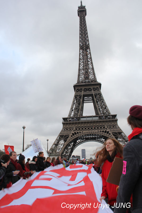 파리회의에서 정의, 재정, 목적면에 있어서 넘어선 안되는 선을 상징하는 붉은 띠를 들고 에펠탑을 향해 행진하고 있다.