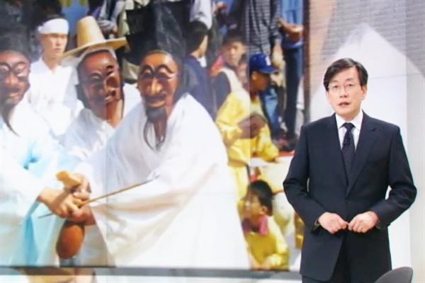 """손석희의 앵커 브리핑 지난 11월 24일, JTBC <뉴스룸>의 앵커 손석희가 '2015 한국 사회의 복면들... 오페라의 유령'이라는 제목의 앵커브리핑을 하고 있는 화면 갈무리. 그는 이날 브리핑에서 국정 교과서 집필진의 비공개를 비판하며 """"탈춤과 마당극은 때로는 권력자를 조롱하기 위해 등장했습니다""""라고 말했다."""