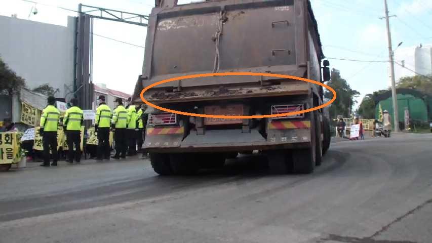 공사장 출입 덤프트럭의 뒷쪽에서 흙이 흘려 내리고 있다. 공사차량에서 떨어진 흙이나 자갈 등이 도로를 오염시킨다.  청소 좀 하세요. 제발.