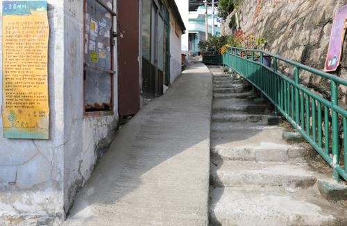 가난한 사람들이 모여사는 바닷가 달동네 목포 서산동의 골목길. 고샅 벽에 김선태 시인의 시 '조금새끼'가 걸려 있다.