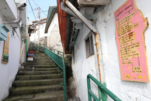 골목길 계단이 급경사를 이루는 목포 서산동 풍경. 길을 따라 시화가 걸려 있다.