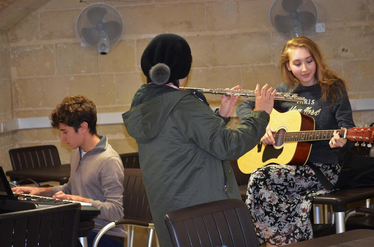 CAS 활동으로 학생들이 모여 길거리에서 연주할 노래를 연습하고 있다.