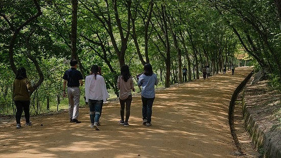 새재 계곡을 따라 만들어진 황톳길. 멀리 앞서 걷고 있는 관광객들은 신발을 들고 맨발로 걷고 있다.