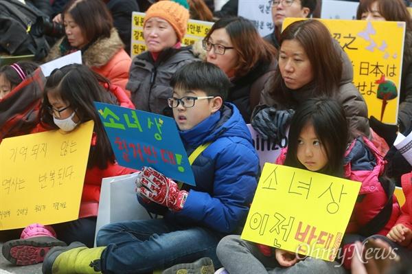 """초등학생도 뿔났다 '소녀상 이전 반대' 6일 정오 서울 종로구 일본대사관 앞에서 열린 '일본군위안부 문제 해결을 위한 1212차 수요집회'에 참석한 초등학생들이 지난달 말 타결한 한일 위안부 문제 협상 폐기와 평화의 소녀상 이전 반대를 요구하고 있다. 이날 열린 1212차 수요집회는 지난 1992년 1월 8일 첫 집회 시작으로 24주년되는 날이며, 지난달 한일 외교장관회담 합의를 규탄하기 위해 전 세계 13개국 41개 지역에서 동시다발로 진행됐다.     이들은 """"피해 당사자인 위안부 할머니들을 배제하고 의견이 묵살된 이번 합의는 절차적 정당성이 결여됐다""""며 """"박근혜 정부는 부당하고 굴욕적인 한일 협상에 대해 국민과 위안부 피해 할머니들에게 사과하고 재협상에 나설 것""""을 촉구했다."""