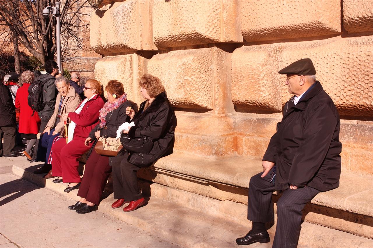 스페인 관광객들이 카를로스 5세 궁전 벽에 등을 기대고 볕을 쬐며 쉬고 있다.