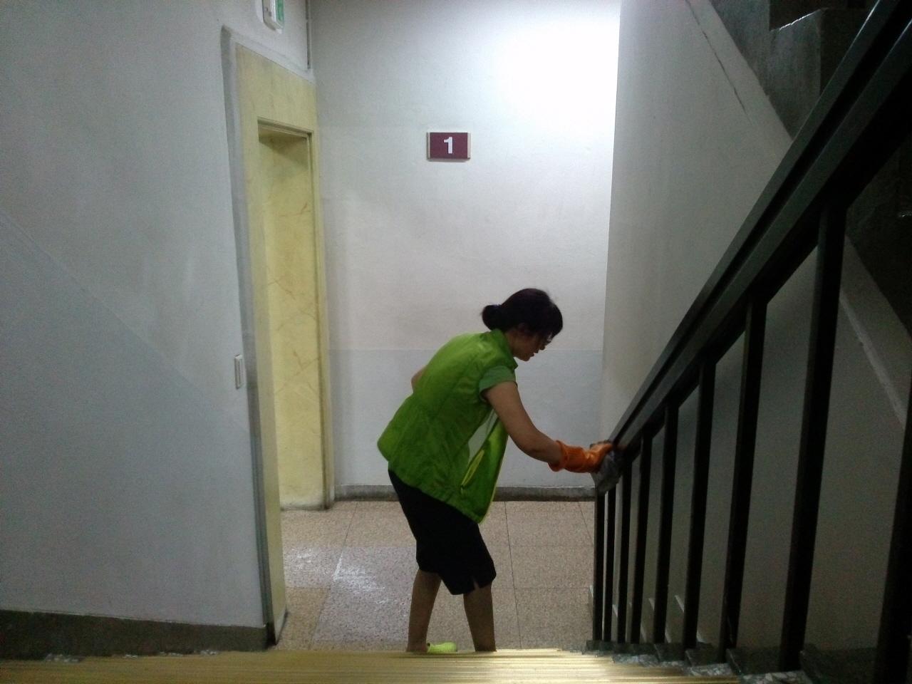 지난여름에 청소노동자가 하계용 근무복을 입고 계단 난간을 닦는 모습이다.