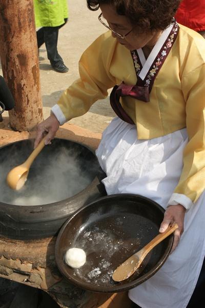 쌀과 밀가루로 만든 덩어리를 뜨거운 물에 익혀내고 있는 삼해주 기능보유자 권희자 장인.
