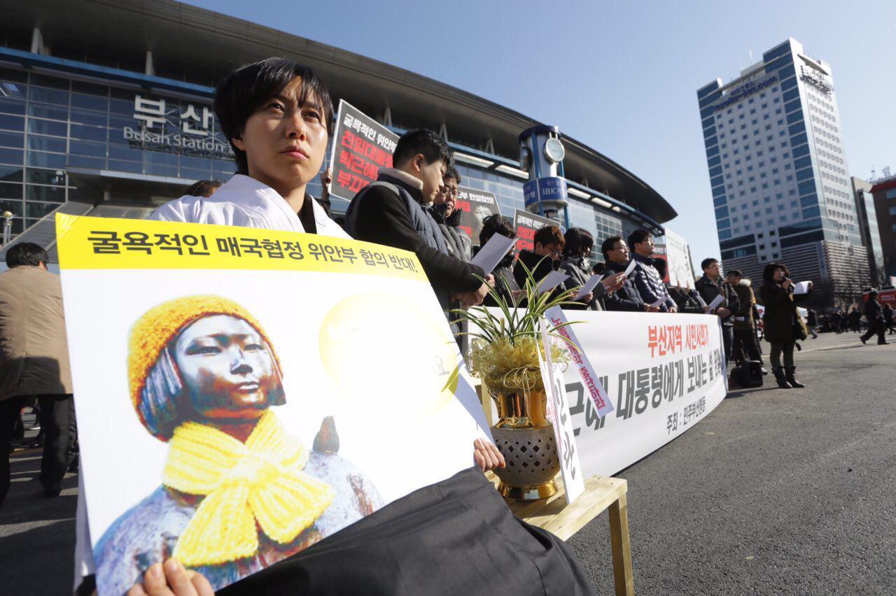 평화의 '소녀상'과 '민란'화분 민주부산행동이 주최한 '박근혜 대통령에게 드리는 설날 선물(민란)'기자회견장에서 위안부'소녀상'복장을 한 대학생이 '민란'화분과 함께 앉아있다.