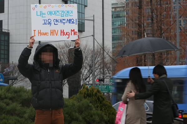 '나는 에이즈 감염인, 안아주세요..'  세계 에이즈의 날(12월1일)을 하루 앞둔 지난 2014년 11월 30일 오후 서울 보신각 앞에서 한 시민이 '나는 에이즈 감염인, 꼭 안아주세요'라고 적힌 팻말을 든 채 프리허그를 요청하고 있다.