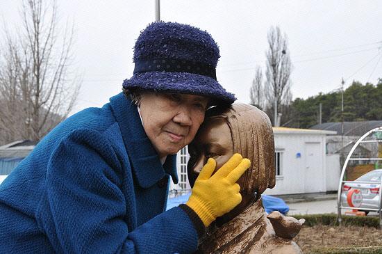 영화 '귀향'의 실제 주인공으로 알려진 강일출 할머니가 지난 8일 아산 평화의 소녀상 제막식 행사에 참석해 소녀상의 뺨을 어루만지고 있다.