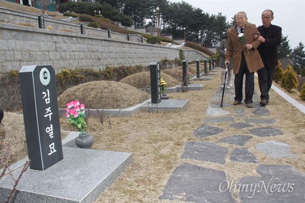 1960년 3월 16일 새벽, 경찰이 눈에 최루탄이 박힌 김주열 열사의 시신을 마산 앞바다에 버릴 당시 짚차를 운전했던 김덕모(76)씨가 13일 오후 국립3.15묘역에 있는 김주열열사 묘소(가묘)를 참배하기 위해 김영만 전 김주열열사기념사업회 회장의 부축을 받으며 걸어오고 있다.