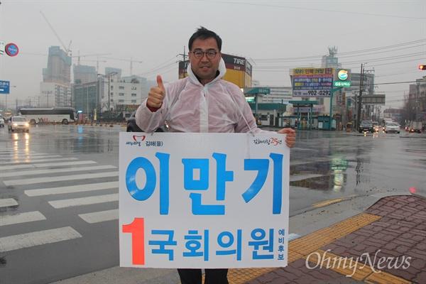 '김해을' 국회의원 선거에 나선 새누리당 이만기 후보가 18일 아침 비가 내리는 속에 김해 장유1동사무소 앞 거리에서 비옷을 입고 출근인사하고 있다.